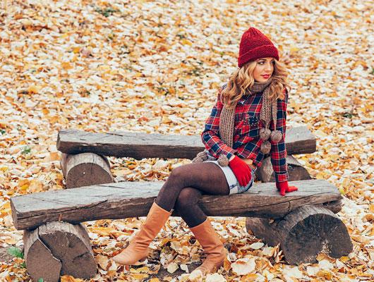 Frau mit rot-blau farblich abgestimmmter Winterkleidung auf einer Bank
